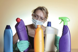 Woman with mask and gloves holding a store bought drain cleaner that is not good for plumbing clogs