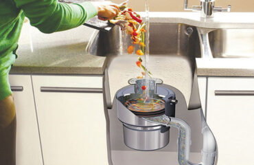This is an image of a person scraping off food from a plate in to the sink to show proper garbage disposal maintenance